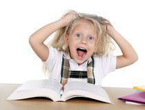 piccola-ragazza-dolce-della-scuola-che-tira-i-suoi-capelli-biondi-nello-sforzo-che-ottiene-pazzo-mentre-studiando-44860017